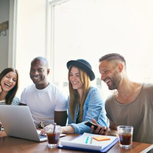 Group of young professionals sat round a laptop laughing