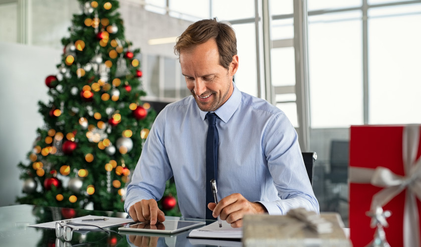 Man working with a Christmas tree in the background
