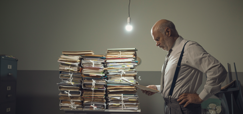 Man staring at a document with a pile of paperwork behind him