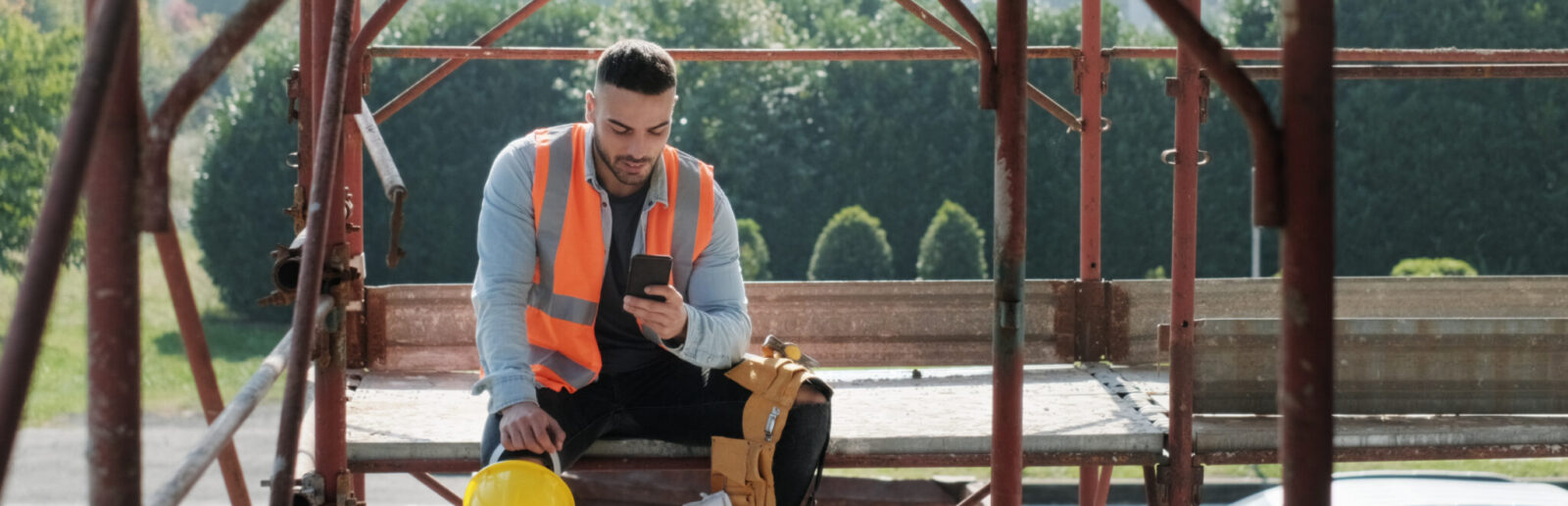Man working in construction site smiling and using smartphone